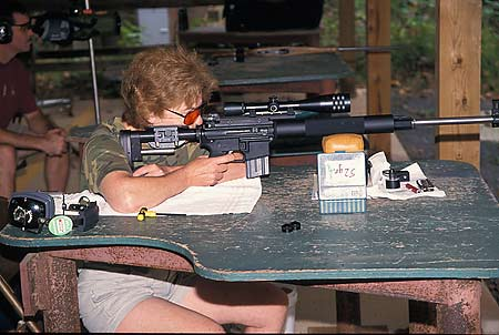 Photograph of Suzanne shooting her custom-made AR-15 match rifle.